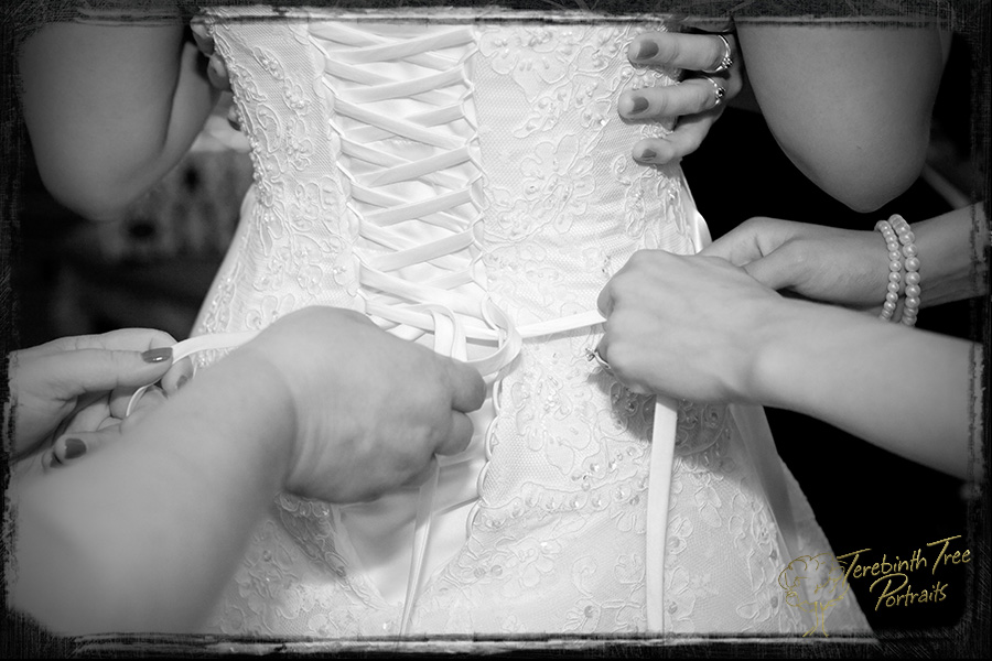 Photo of the bride's wedding dress being laced up at her wedding at the Pala Mesa Resort in Fallbrook