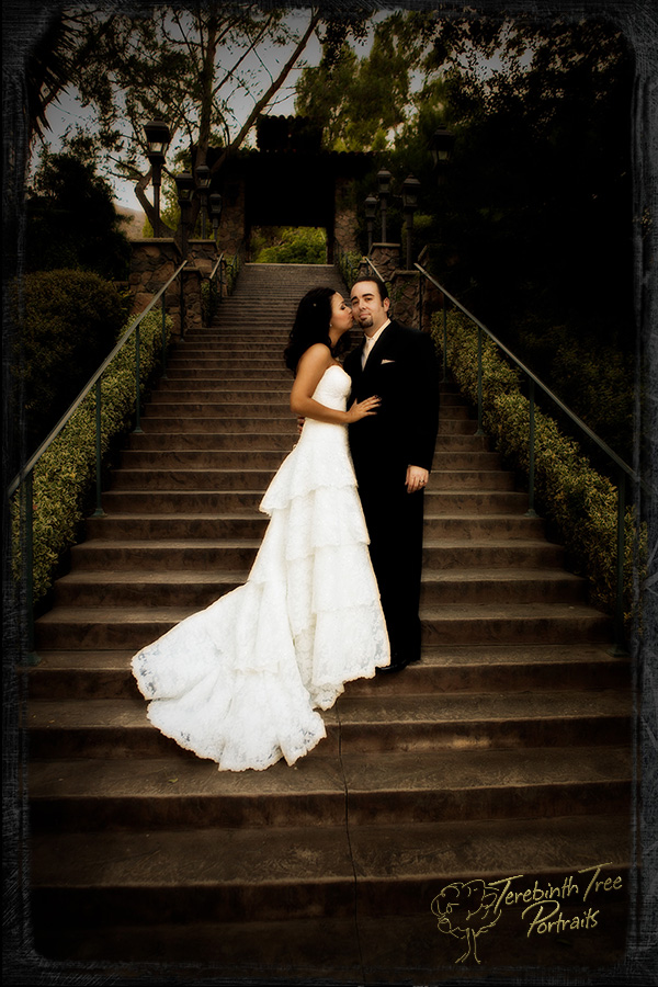 Wedding photo of Megan kissing Matt's cheek while standing on the big stairs at the Pala Mesa Resort in Fallbrook.