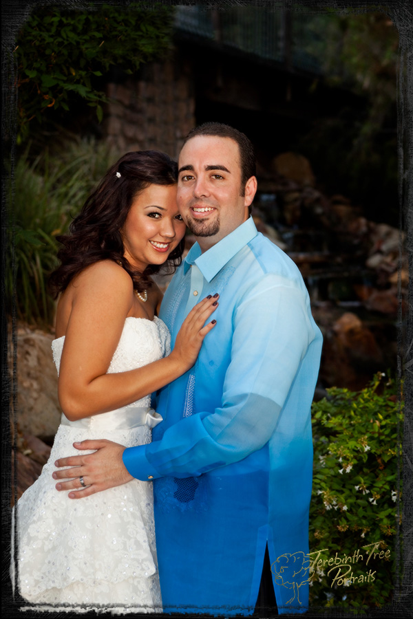 Photo of Megan and Matt at their wedding posing in front of a waterfall at the Pala Mesa Resort in Fallbrook