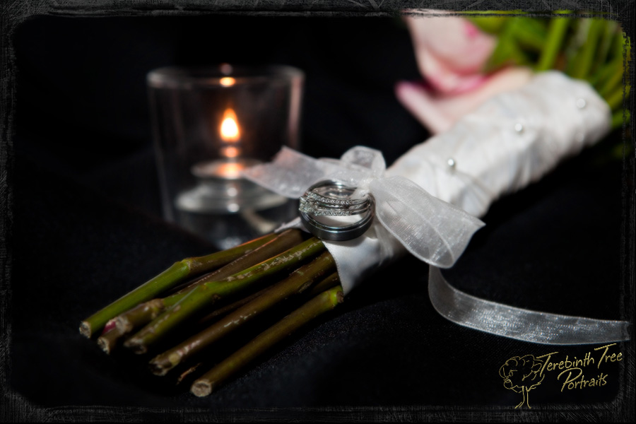Closeup photo of Megan and Matt's wedding rings and bouquet at their wedding in Fallbrook