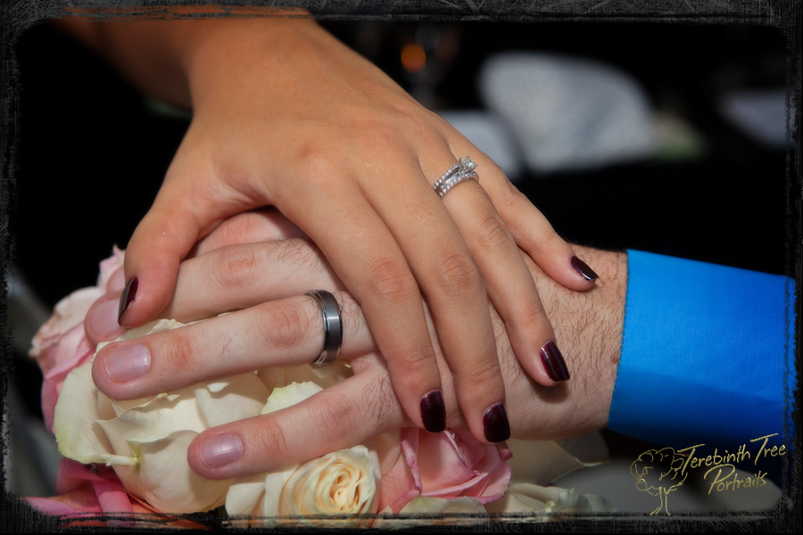 Closeup photo of Megan and Matt's hands with rings over the bride's bouquet at their wedding at the Pala Mesa Resort in Fallbrook