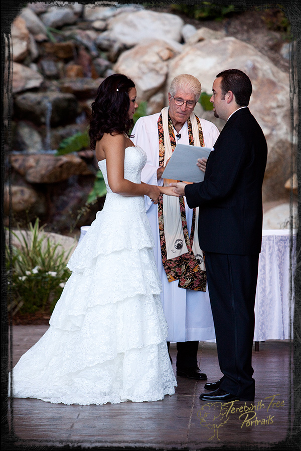Photo of the bride and groom exchanging rings during their wedding ceremony at the Pala Mesa Resort in Fallbrook